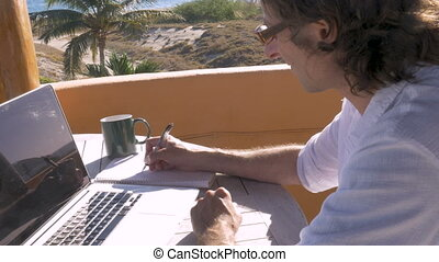 Man writing with pen and paper while working on computer...
