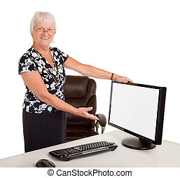 Senior Businesswoman Pointing at a Blank Monitor - A senior...
