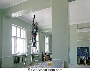 painter - man standing on a ladder and paint the ceiling and...