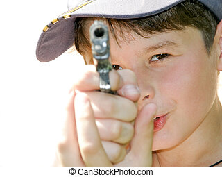 a boy shoots a toy pistol - shallow depth of field, focus on...