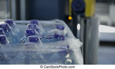 Process of packaging plastic bottles with water on conveyor...