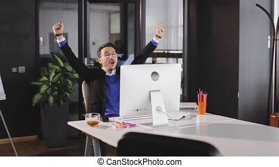 Man excited jumping and raising hands when successfully...