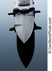 Combat knife - Battle metal folding knife on the background...