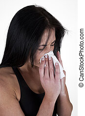 Woman sneezing into a tissue - Woman sneezing into a tissue...