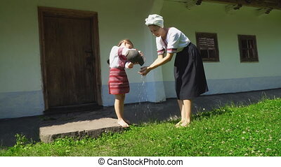 daughter pours water on her mother's hands - daughter pours...