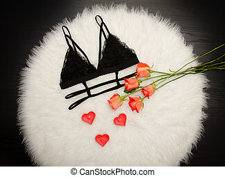 Black lace bra on white fur and a bouquet of orange roses....