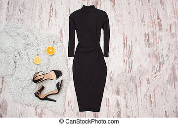Black dress with a sleeve, shoes and halves of an orange on...