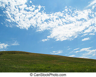 Rolling green hills under a blue summer sky