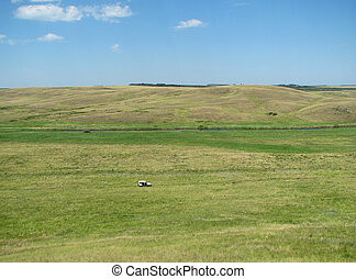 Rolling green hills under a blue summer sky with car
