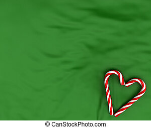 Heart made from christmas candies on green background