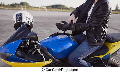 The motorcyclist wears special leather gloves for riding a...