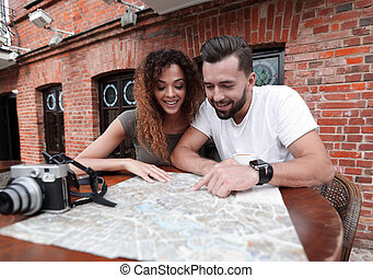 Couple in an outdoor cafe using map and planning itinerary -...