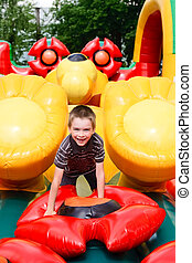 Boy in inflatable playground - Young boy playing in...