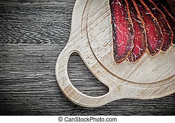 Sliced steak wooden carving board food concept.