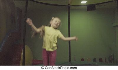 children jumping on a trampoline in the playroom