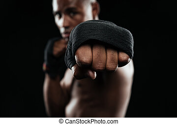 Afroamerican kickboxer ready to fight on black background
