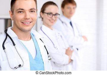Cheerful smiling male doctor with medical staff at the...