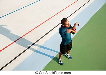 Top view portrait of a young african sportsman stretching...