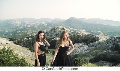 two beautiful young women in posh black dresses posing...