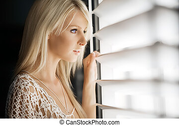 Waiting - Beautiful young woman looks out through blinds