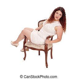 Full figured woman sitting in armchair - A young pretty...