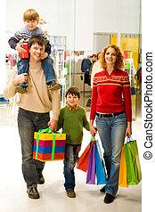 Shopaholics - Portrait of family walking down shopping mall...