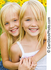 Affection - Portrait of cute girl embracing her twin sister...