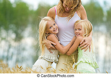Having fun - Twin sisters embracing their mother with smiles...