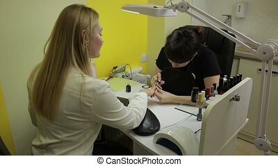 Attractive manicurist applying red nail polish - Attractive...