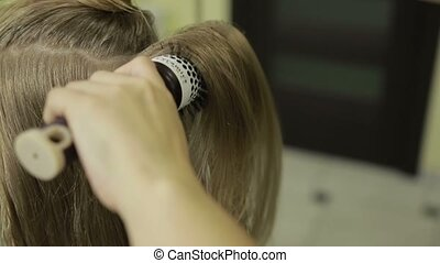 Hairstylist brushing long blonde hair of client - Closeup...