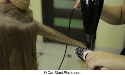 Hairstylist drying client's hair in beauty salon - Closeup...