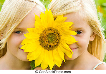 Sunflower children - Close-up of pretty twins looking at...
