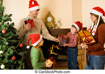 Giving presents - Portrait of parents and sons wearing santa...