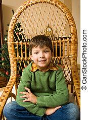 Little boy - Portrait of boy sitting in wicker chair and...