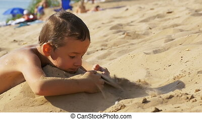 The Child is Playing with Sand on the Beach in Slow Motion -...