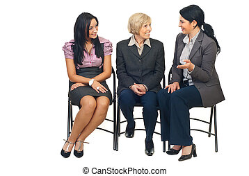 Three business women having conversation at conference and...