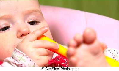 baby with rattle - close-up small baby with rattle toy in...