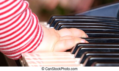 baby playing with piano - close-up six month baby strike to...