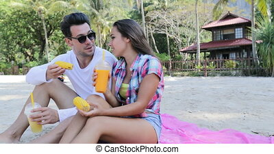 Couple On Beach Eat Tropical Fruits Drink Juice Talking Sit...