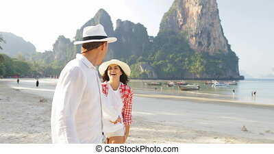 Man Leading Woman Couple Walking On Beach Holding Hands...