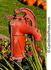 Old red water pump - An old red handled water pump in a...
