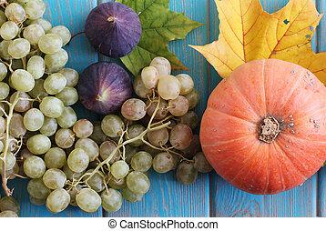Composition of vegetables on blue wooden desk. Pumpkin, fig,...
