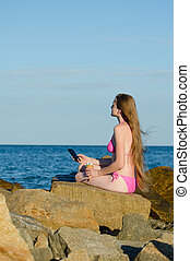 Thoughtful young woman sitting on the rocks with a telephone...
