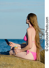 Thoughtful girl in a bathing suit sitting on the rocks with...