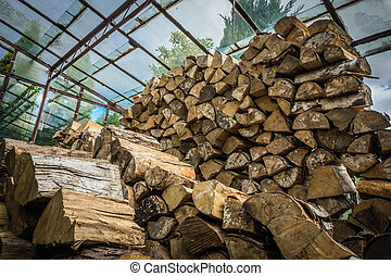 Firewood stacked in huge piles in hothouse - Firewood...