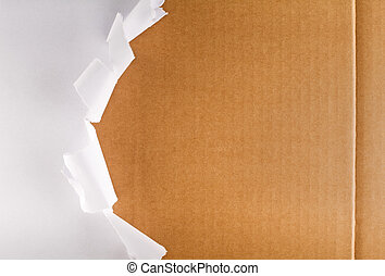 Torn packaging paper revealing cardboard box - Torn wrapping...