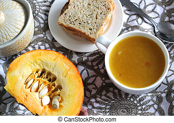 Pumpkin soup in white mug on table. Modern photography. The...