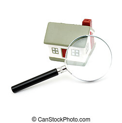 A magnifying glass examining model home. Isolated on white.