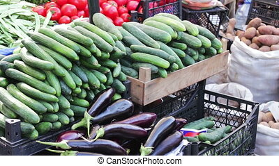 Lot of fresh vegetables on the market counter. Buyers look...