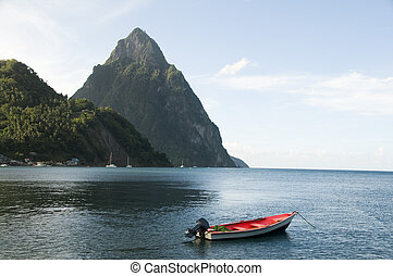 Caribbean Sea native fishing boat with view twin piton peaks...